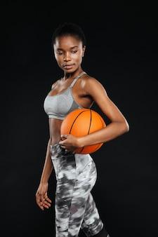 Retrato de uma mulher esportiva posando segurando uma bola de basquete isolada em uma parede preta