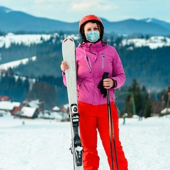 Retrato de uma mulher esquiadora em máscara médica no contexto das montanhas dos cárpatos 2021