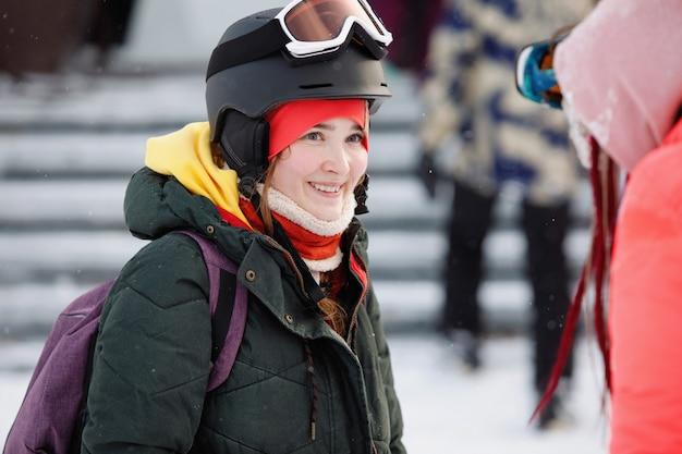 Retrato de uma mulher esquiadora, snowboarder com um capacete, óculos e um chapéu de malha