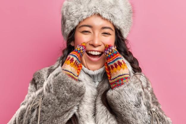 Retrato de uma mulher esquimó feliz e alegre usa um casaco de inverno e luvas de tricô exclamando alegremente, olha positivamente para a frente mora no extremo norte isolado sobre uma parede rosa
