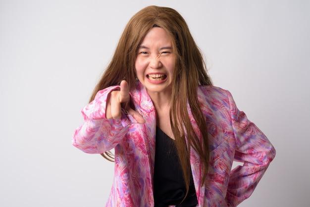 Retrato de uma mulher estranha usando terninho rosa e peruca contra uma parede branca