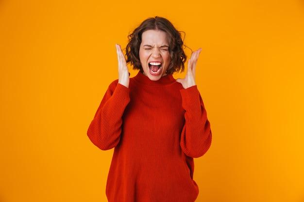 Retrato de uma mulher estressada na casa dos 20 anos, vestindo um suéter, gesticulando e gritando enquanto ficava em pé, isolado sobre o amarelo