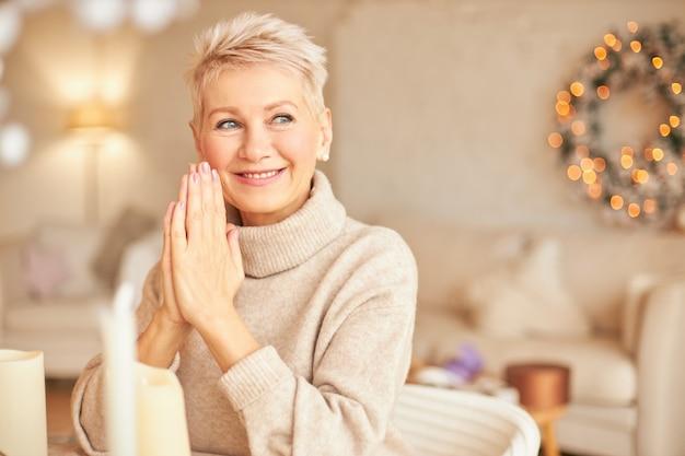 Retrato de uma mulher europeia de meia-idade atraente e feliz com uma maquiagem elegante e um corte de cabelo elegante, sentado na sala de estar com uma coroa de flores de pinho e uma guirlanda