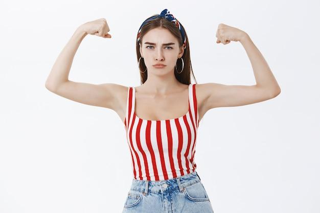 Retrato de uma mulher europeia elegante, forte e confiante, bonita, com um top listrado e uma faixa na cabeça franzindo os lábios e franzindo a testa fazendo uma careta mostrando os músculos e os bíceps