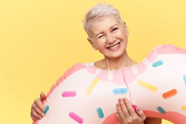 Retrato de uma mulher europeia madura e emocional com um penteado de duende carregando um círculo rosa inflável em forma de donut, fazendo uma careta engraçada como se estivesse mordendo, se divertindo, aproveitando o verão