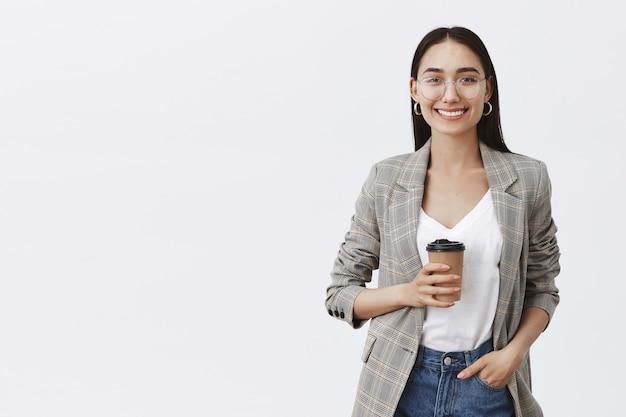 Retrato de uma mulher europeia relaxada e confiante com cabelos escuros e óculos, segurando a mão no bolso e bebendo chá