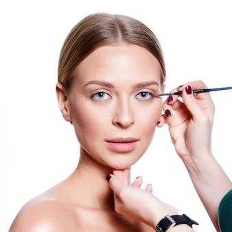 Retrato de uma mulher fazendo a maquiagem