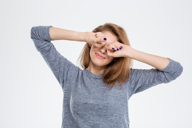 Retrato de uma mulher feliz acordando e esticando as mãos isoladas em um fundo branco