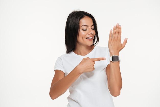 Retrato de uma mulher feliz, apontando o dedo no relógio inteligente