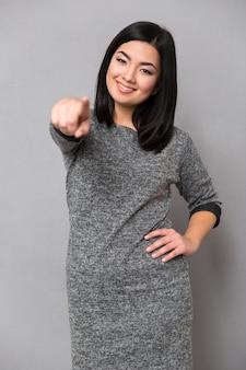Retrato de uma mulher feliz apontando o dedo para a frente por cima de uma parede cinza
