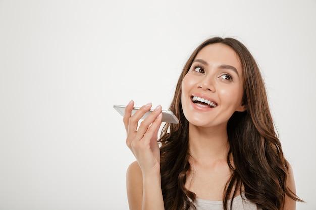 Retrato de uma mulher feliz com cabelos castanhos compridos, falando no celular, tendo agradável diálogo móvel isolado sobre o branco