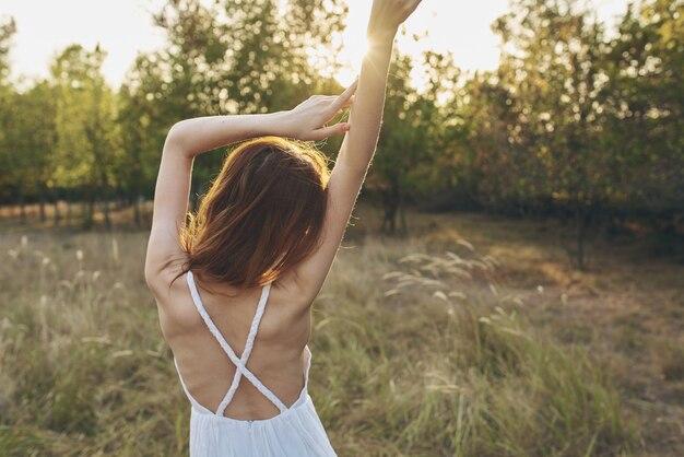 Retrato de uma mulher feliz com um vestido de verão em um ano de campo por trás do pôr do sol de árvores.