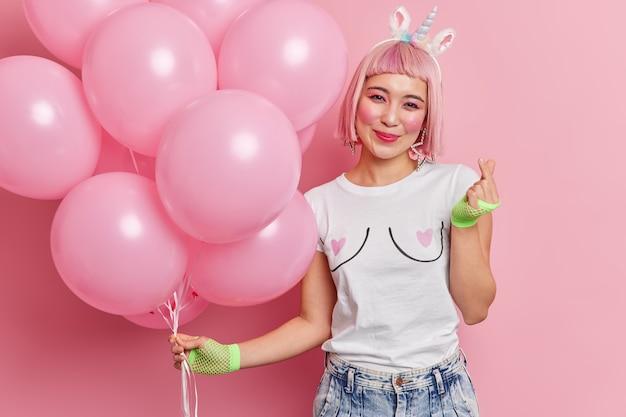 Retrato de uma mulher feliz de cabelo rosa com aparência oriental gestos gestos de minissinal poses com balões de hélio curtindo as férias vestida com roupas da moda