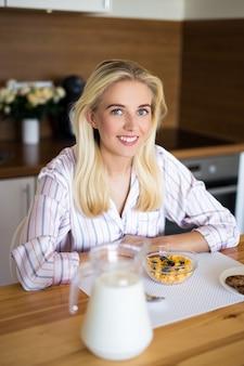Retrato de uma mulher feliz de pijama sentada em uma cozinha moderna