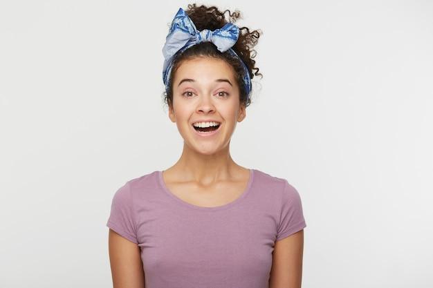 Retrato de uma mulher feliz de repente encantada com uma expressão positiva, vestida com uma camiseta casual e uma tiara estilosa