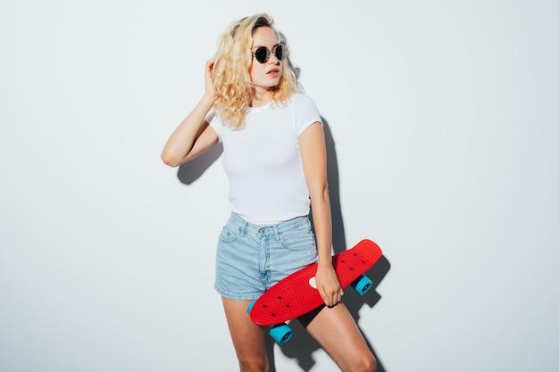 Retrato de uma mulher feliz e alegre em óculos de sol, posando com um skate em pé sobre uma parede branca