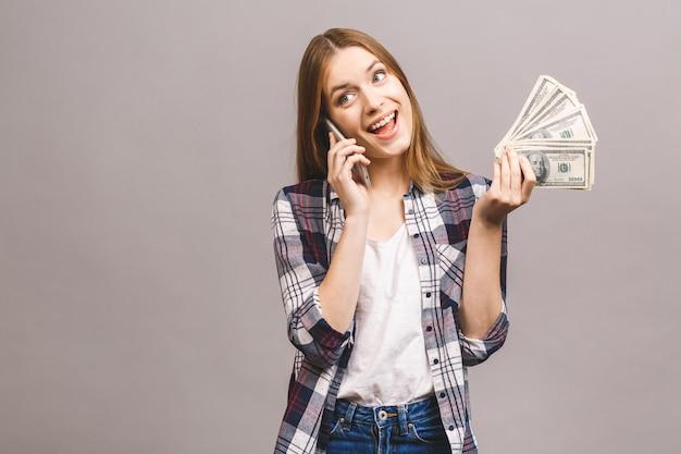 Retrato de uma mulher feliz e animada falando no celular enquanto segura o monte de notas de dinheiro.