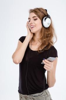 Retrato de uma mulher feliz e casual ouvindo música em fones de ouvido em um smartphone isolado em um fundo branco