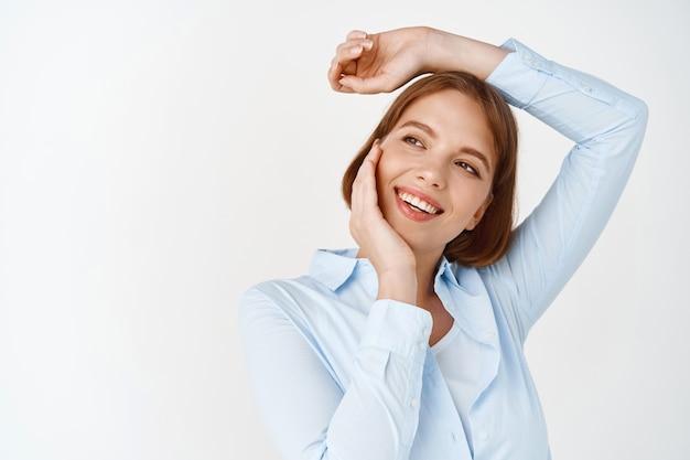 Retrato de uma mulher feliz e despreocupada em uma blusa, descansando a mão na cabeça e tocando o rosto de beleza natural, sorrindo