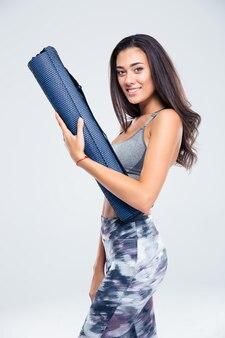 Retrato de uma mulher feliz e fitness segurando um tapete de ioga isolado em uma parede branca
