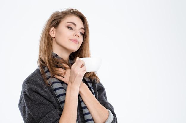 Retrato de uma mulher feliz e fofa segurando uma xícara com café isolado em um fundo branco