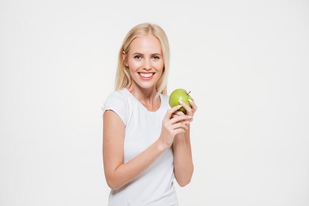 Retrato de uma mulher feliz e saudável segurando a maçã verde