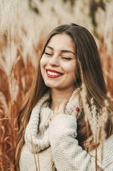 Retrato de uma mulher feliz e sorridente com os olhos fechados no outono no campo.