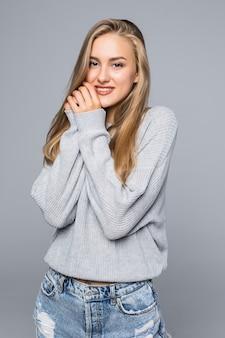 Retrato de uma mulher feliz e sorridente em um suéter com as mãos perto do rosto, olhando para longe, isolado no fundo cinza