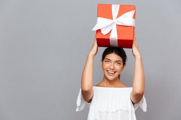 Retrato de uma mulher feliz e surpresa com uma caixa de presente na cabeça, olhando para a frente, isolada em uma parede cinza