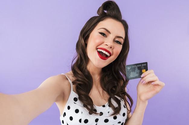 Retrato de uma mulher feliz em um vestido vintage de bolinhas sorrindo enquanto segura um cartão de crédito de plástico isolado sobre a parede violeta