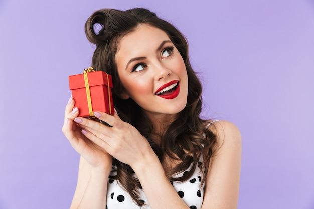 Retrato de uma mulher feliz em um vestido vintage de bolinhas sorrindo enquanto segura uma caixa de presente vermelha isolada sobre a parede violeta