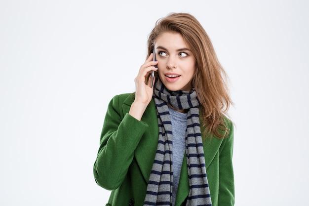 Retrato de uma mulher feliz falando ao telefone e olhando para longe, isolado em um fundo branco