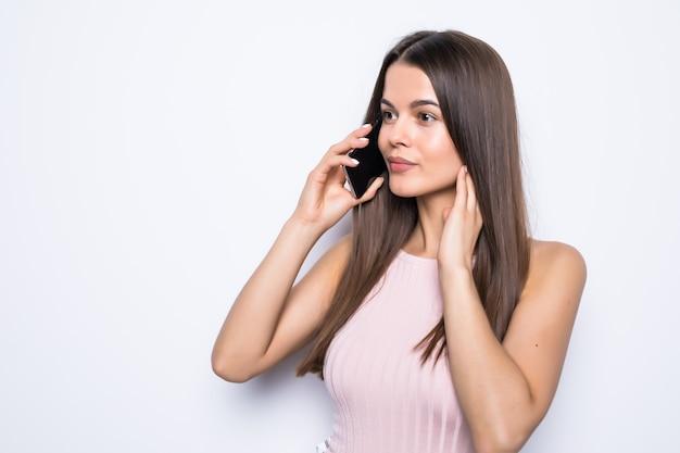 Retrato de uma mulher feliz falando ao telefone, sobre uma parede branca.