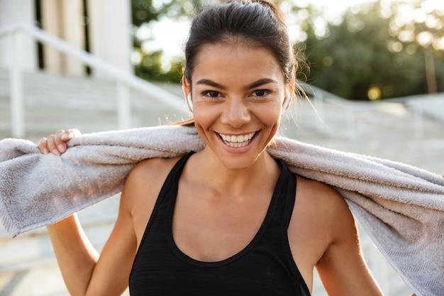 Retrato de uma mulher feliz fitness com toalha descansando