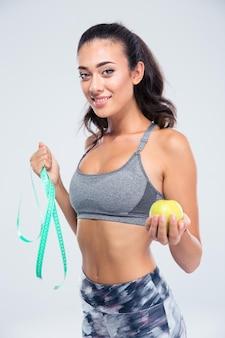 Retrato de uma mulher feliz fitness segurando uma maçã e medindo o tipo isolado em uma parede branca