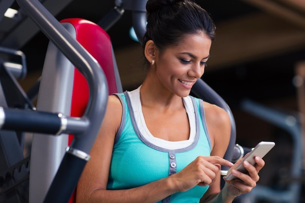 Retrato de uma mulher feliz fitness usando smartphone na academia
