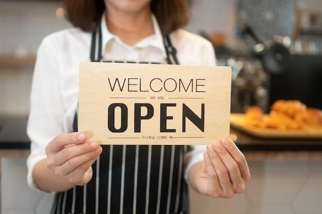 Retrato de uma mulher feliz, garçonete asiática em pé em uma cafeteria segurando uma placa aberta enquanto reabrindo o atendimento durante a pandemia de coronavírus, proprietário de uma pequena empresa e iniciante com um conceito de cafeteria