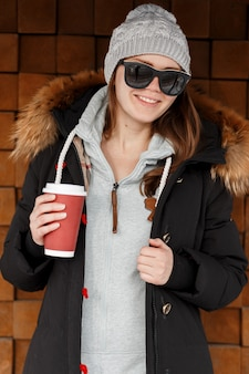 Retrato de uma mulher feliz jovem hippie em óculos de sol com chapéu de malha em uma jaqueta elegante de inverno com um capuz de pele com uma xícara de café nas mãos dela. linda garota alegre bebe bebida quente.