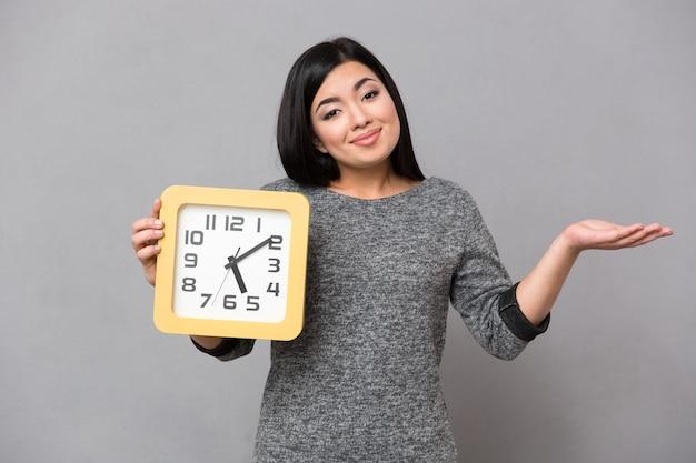 Retrato de uma mulher feliz segurando um relógio de parede e copyspace na palma da mão sobre uma parede cinza