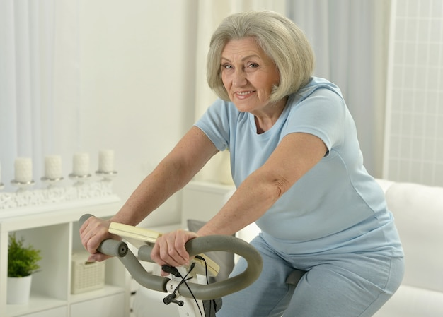 Retrato de uma mulher feliz sênior fazendo exercícios de bicicleta