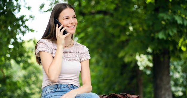 Retrato de uma mulher feliz, sentado no banco e falando ao telefone ao ar livre