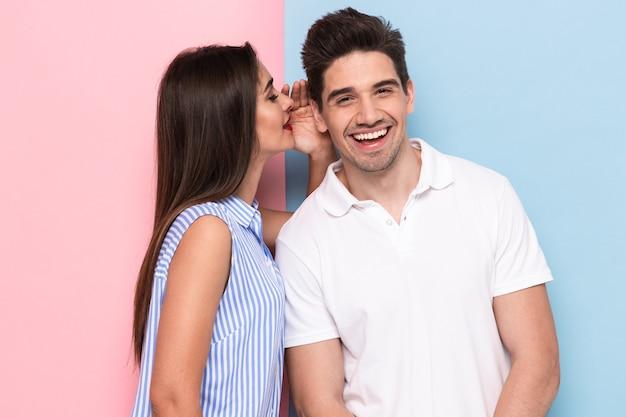 Retrato de uma mulher feliz sussurrando um segredo ou uma fofoca interessante para um homem bonito em seu ouvido, isolado sobre uma parede colorida