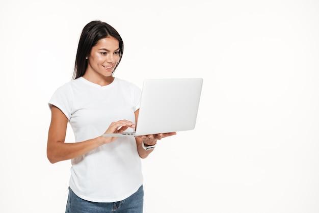 Retrato de uma mulher feliz usando o computador portátil em pé