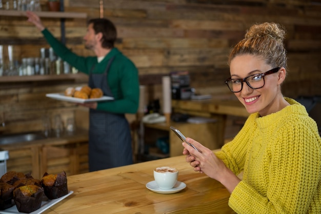 Retrato de uma mulher feliz usando um telefone celular enquanto um barista trabalhava em segundo plano em uma cafeteria