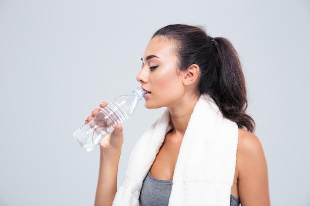 Retrato de uma mulher fitness com toalha de água potável isolada em uma parede branca
