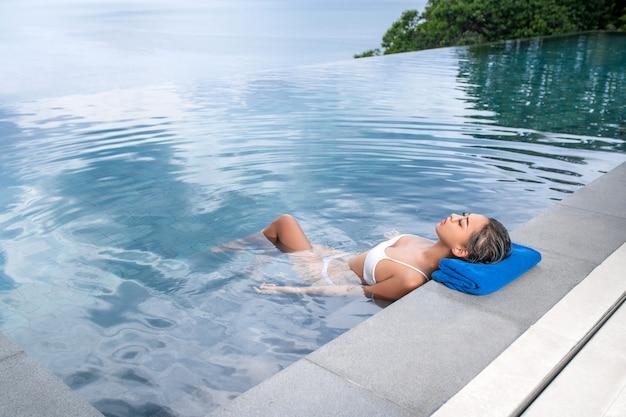 Retrato de uma mulher flutuando na piscina e descansando a cabeça em uma toalha. relaxe e spa