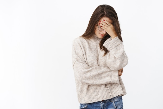 Retrato de uma mulher fofa irritada e farta de suéter e óculos fazendo gesto no rosto com a palma da mão