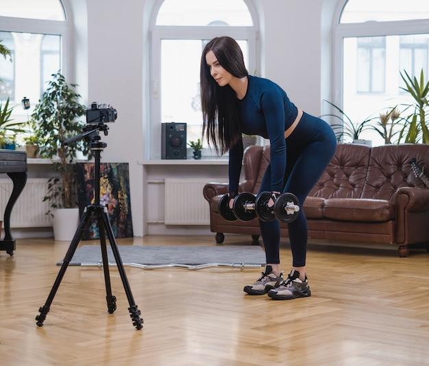 Retrato de uma mulher forte e esportiva com roupas azul escuro que posa na câmera levantando halteres.