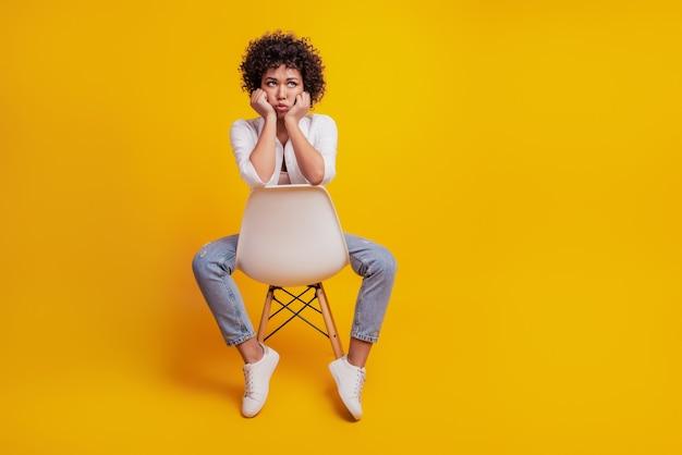 Retrato de uma mulher frustrada chorando, sente-se na cadeira e de mau humor na parede amarela