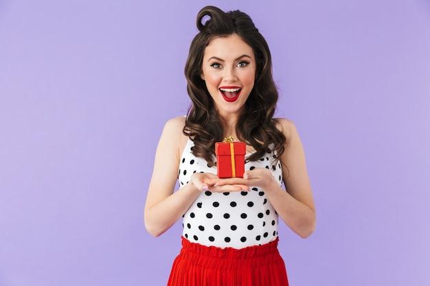 Retrato de uma mulher glamourosa com um vestido de bolinhas vintage, sorrindo enquanto segura uma caixa de presente vermelha isolada sobre a parede violeta